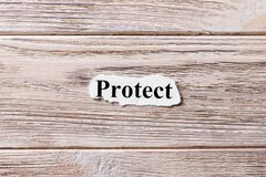 Protect of the word on paper. concept. Words of Protect on a wooden background.  Royalty Free Stock Photo