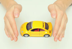 Protect your car. Woman hands holding yellow car royalty free stock photos
