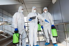 Men in protective suits deciding what to disinfect with spray