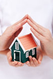 Protect your home. Small house shielded with hands stock image