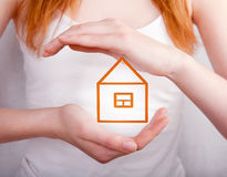 Protect your home -house shielded with hands. Protect your home - small house shielded with hands Stock Photography