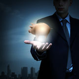 Protect your money. Close up of businessman holding piggy bank in palm Royalty Free Stock Images