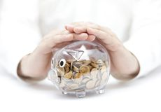 Protect your money. Transparent piggy bank with coins covered by hands stock photography