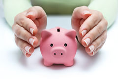 Protect your savings - with hands and piggy bank. With woman Stock Image