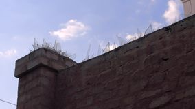 Protected area with bick wall and sharp glass. On blue sky stock video