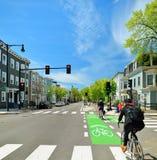 Protected Bike Lane in City Street. Protected bike lane between parking lane and sidewalk Stock Photo