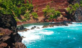 Red sand waves crashing over a rocky outcropping Royalty Free Stock Images