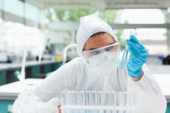 Protected female scientist looking at a test tube Royalty Free Stock Images