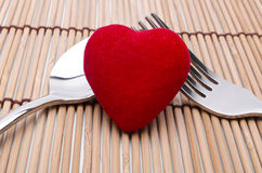 Protected love. Red heart in front of silver fork and spoon royalty free stock image
