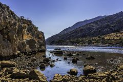 Protected natural harbour as seen behind rocks, shot low, under clear blue skies Stock Images