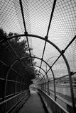 Protected walkway. Inside view of a covered metal fence pedestrian overpass Royalty Free Stock Photography
