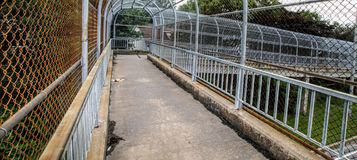Enclosed walkway. Inside view of a covered metal fence pedestrian overpass Stock Photography