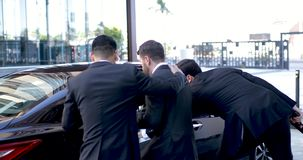 Protecting businessman from danger. Couple of agents with guns protecting an important businessman from danger and getting him into a car stock video