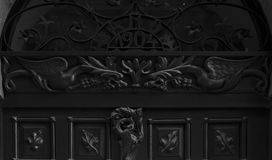 Protecting dragons on the main door. Shot in black and white, detail on the sculpture on the facade of this historic building representing some characters. Set Royalty Free Stock Photo