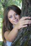 Protecting friend. Beautiful girl hugging a tree, concept of unity with nature stock photo