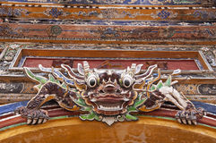 Protecting the Gate. Above the side gate of the Forbidden Purple City in the Citadel of Hue, Vietnam, is this fierce protector. There are three protectors of the royalty free stock image