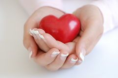 Protecting A Heart. Young woman with beautiful long nails holding a wooden red heart Royalty Free Stock Images