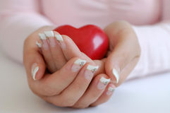 Protecting A Heart. Young woman with beautiful long nails holding a wooden red heart Stock Photography