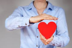 Protecting a heart. A person holding and protecting a heart symbolizing safety, love and health Stock Image