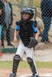Protecting home plate during the game. Little league catcher in protective mask and chest pad looking alert toward the next play at home royalty free stock image