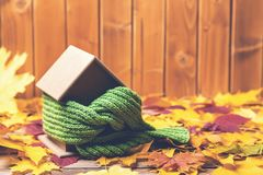 Protecting and isolating house. Scarf around house model on wooden table. Small miniature of house in warm scarf on autumn leaves. Background. Preparing the royalty free stock photo