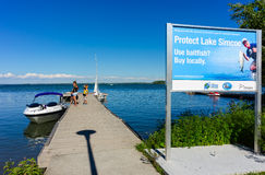 Protecting lake from invasive species. Family boarding a pleasure boat from a dock at the Sibbald Provincial Park at Lake Simcoe, beside a sign warning about Stock Images