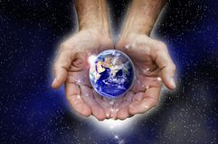 Protecting planet earth. A man's cupped hands hold the earth as the sun breaks on the horizon.  Stars are around the hands and trickling down from the fingers Royalty Free Stock Photo