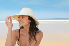 Protecting from the sun at the beach. Beautiful woman sitting on the beach with straw hat Stock Photos