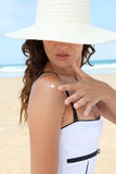 Protecting from the sun at the beach. Beautiful woman putting sunscreen on her shoulder Royalty Free Stock Photo