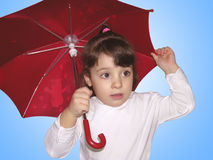 Protection. A beautiful little girl holding a red umbrella above her head Stock Images