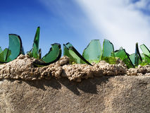 Protection against intruders. Sharp pieces of glass in mortar on top of a wal Stock Image