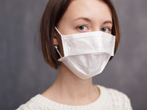 Protection against viruses and bacteria during the flu epidemic. Girl in medical disposable mask looking at the camera Stock Photography