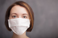 Protection against viruses and bacteria during the flu epidemic. Girl in medical disposable mask looking at the camera Royalty Free Stock Photo