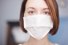 Protection against viruses and bacteria during the flu epidemic. Girl in medical disposable mask looking at the camera Stock Photo