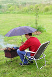 Protection brazier from rain. Teenage boy holding an umbrella over a brazier with burning firewood royalty free stock photography