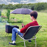 Protection brazier from rain. Teenage boy holding an umbrella over a brazier with burning firewood Stock Images