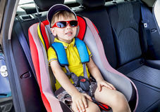Protection in the car. Caucasian child is sitting and fastening with security belt in safety car seat. Protection in the car. Caucasian child in the sunglasses Royalty Free Stock Images