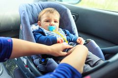 Protection in the car. woman is fastening security belt to child, who is sitting in safety car seat. Protection in the car. women is fastening security belt to stock photo
