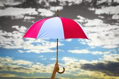 Protection concept: hand holding rainbow umbrella distinctively unique. Drought concept: blue sky and white clouds and dry land stock image