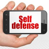 Protection concept: Hand Holding Smartphone with Self Defense on display. Protection concept: Hand Holding Smartphone with red text Self Defense on display, 3D Stock Photo