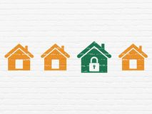 Protection concept: home icon on wall background. Protection concept: row of Painted orange home icons around green home icon on White Brick wall background Stock Photo