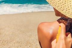 Protection de crème de Sun Équipez la crème du soleil de pulvérisateurs sur l'épaule du ` s de femme Concept de soin de peau Peau photographie stock libre de droits