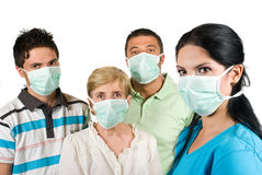 Protection from flu. Young woman with protective mask standing in profile and in front of image looking at you and other three people with mask near her concept Stock Photo