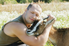 Protection and love to animals. Man embraces a domestic goat Stock Photo