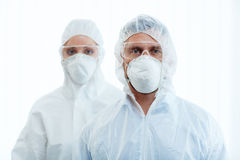 Protection. Man and women in protective masks, eyeglasses and coveralls Stock Photos