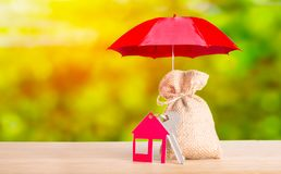 Protection money and saving business concept. Red umbrella cover red house with key and bag from sacking on green sunny background royalty free stock photos