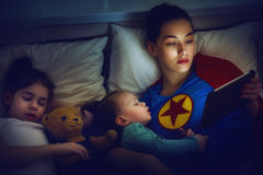 Protection of the mother superhero. Adorable little children girls are napping in the bed with their mom. Quiet sleep with teddy bear under the protection of the Royalty Free Stock Image
