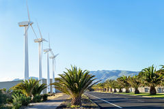 Protection of nature. Wind turbines against mountains and near road. Stock Photography