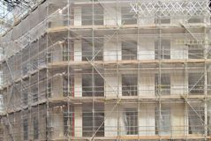 Protection net structure covering building on construction site. royalty free stock photo