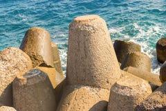 Protection puissante de grand de ciment brise-lames de bloc du littoral contre les vagues orageuses de la mer sur un fond d'azur photographie stock